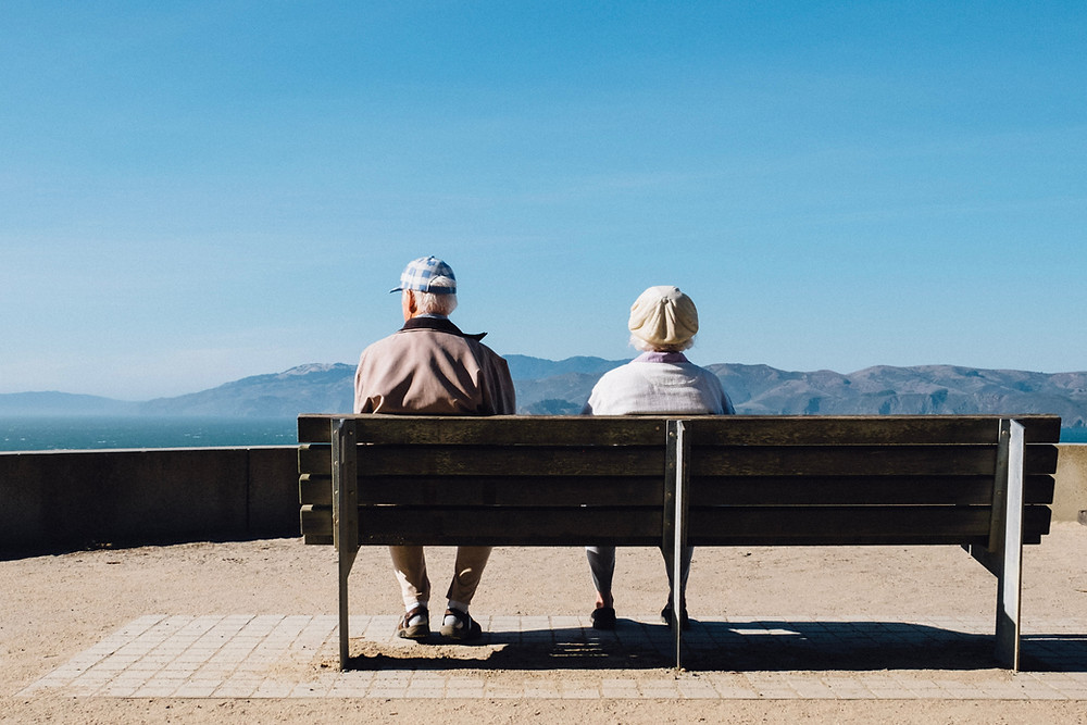 An elderly couple watching the mountains from a bench.