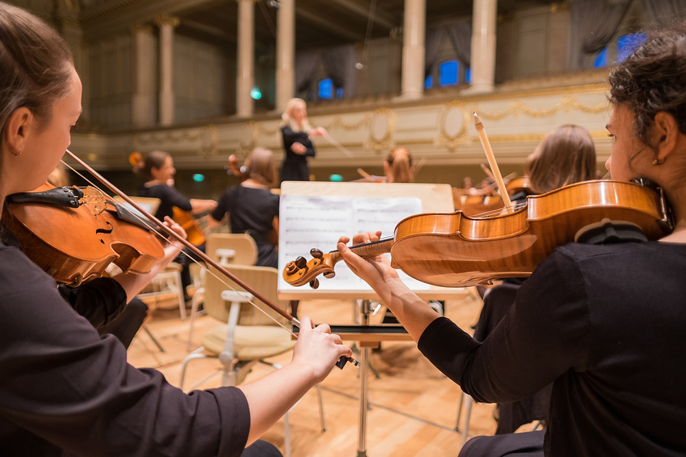 Close up of violin players within an orchestra