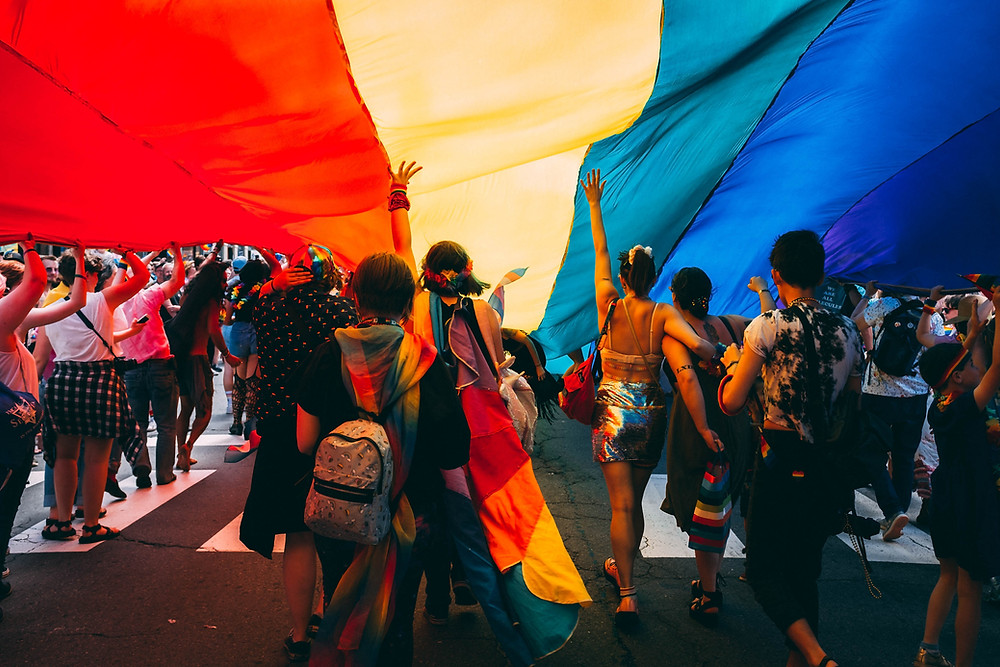 People moving foward in a parade underneath a huge LGBTQ flag