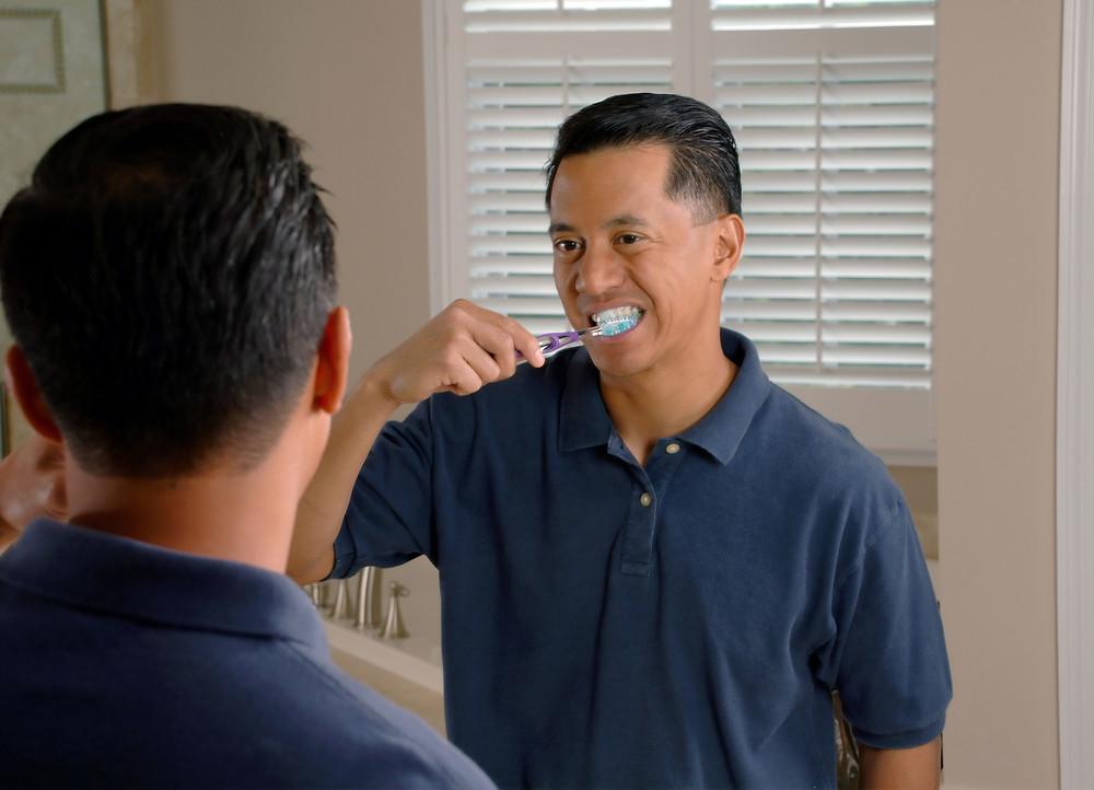 man brushing his teeth in front of mirror