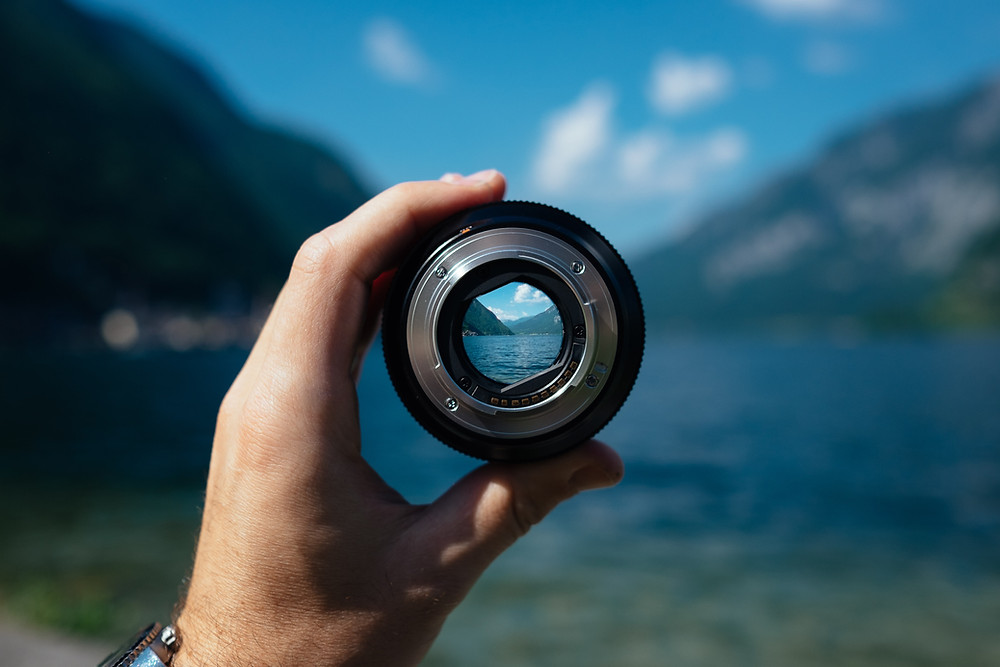 A Lake between two mountains, it is out of focus. In the centre of the image a hand is holding up a camera lens, through the lens the picture beyond is cystal clear.