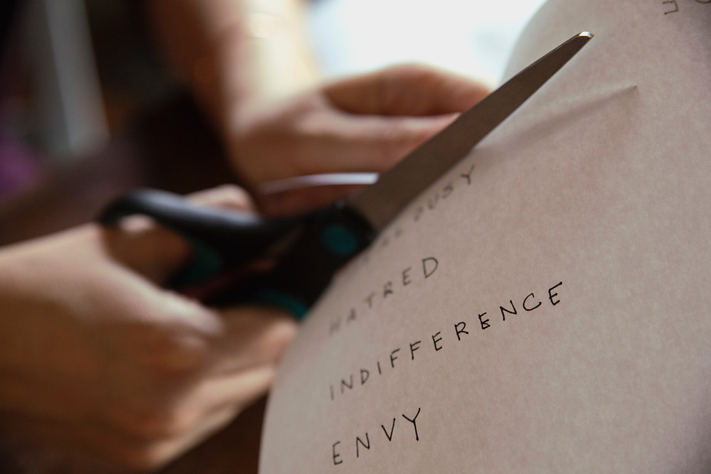 Person cutting up paper with emotional words on it: Hatred, indifference, envy