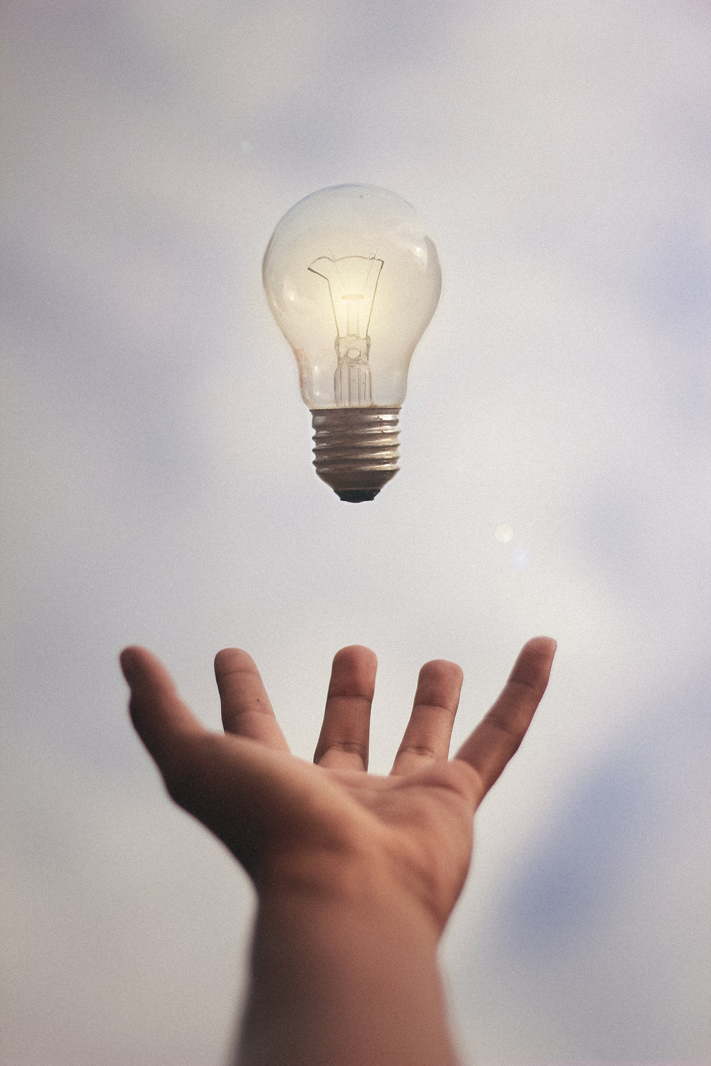 Light bulb hovering over an outstretched hand.