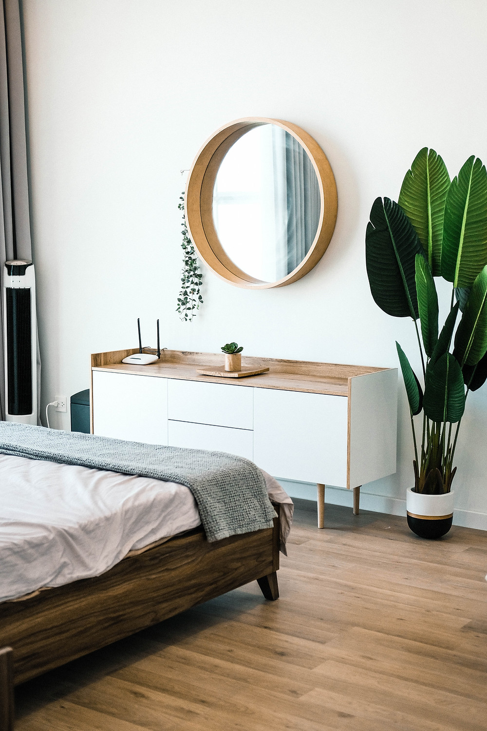 A neat bedroom with natural wood floors and a wooden bedframe. Neutral colours with a large banana leaf plant, A dresser stands tidily with a large round mirror above it.