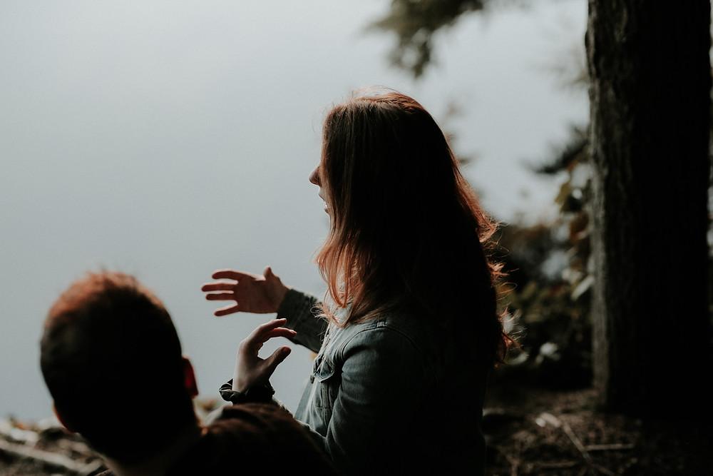 Woman and man talking near lake.