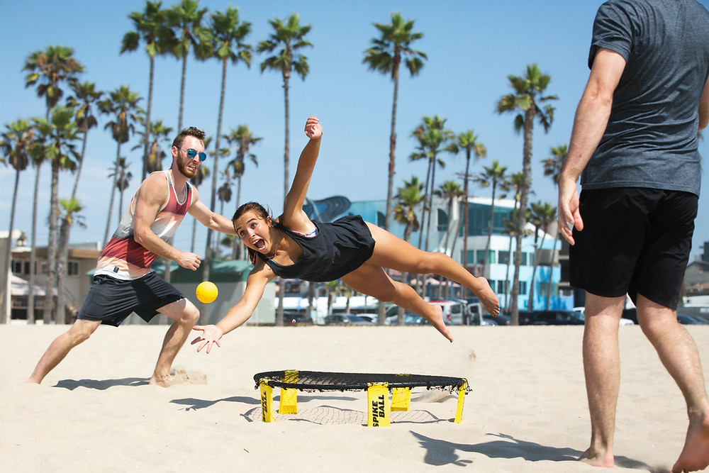 Group of friends playing spike ball on the beach
