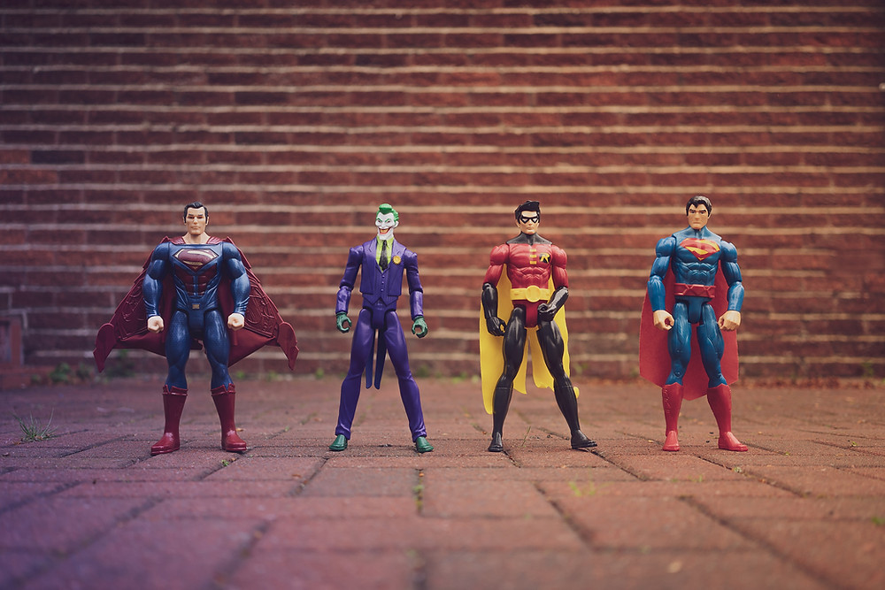 Superman, Joker, Robin and Superman action figures lined up against a brick wall.