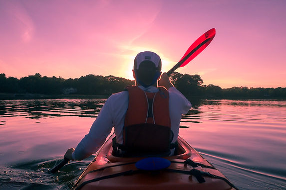 Kayaker paddling through calm waters with pink and purple sunset sky