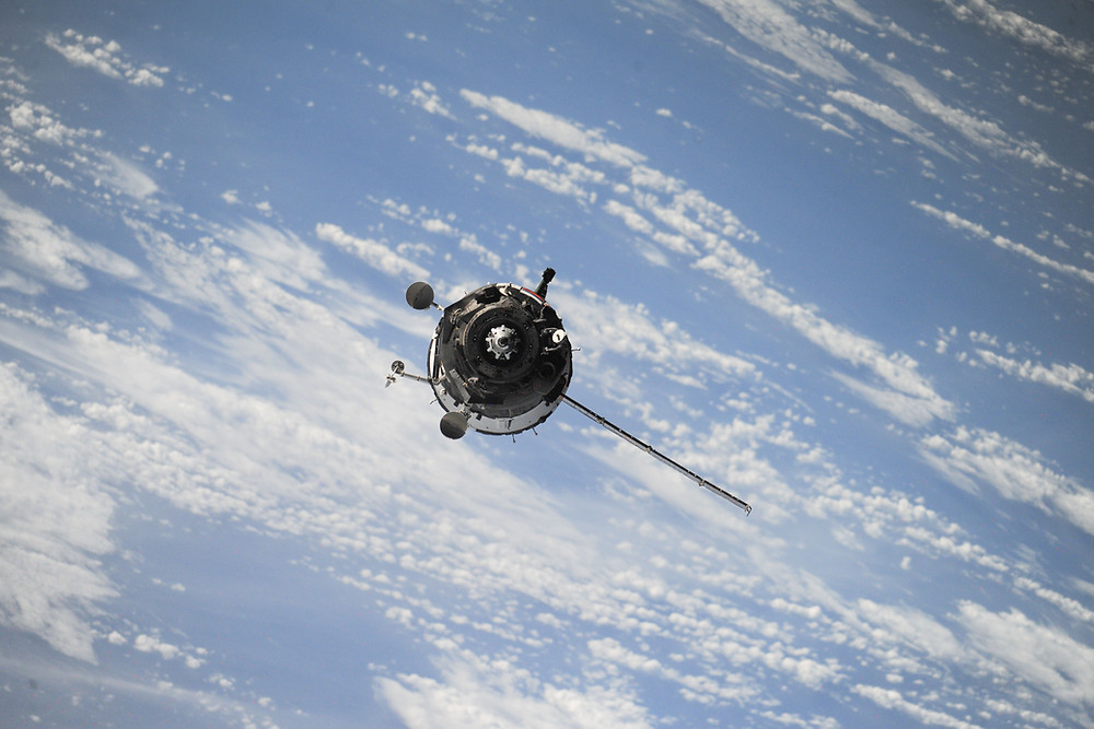 Satellite with blue sky and clouds background.