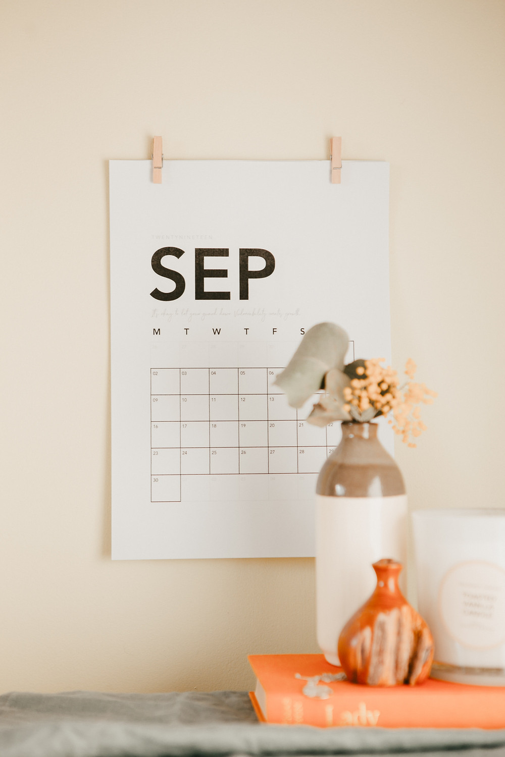 a wall calendar turned to September with a book, flower, and vases in foreground