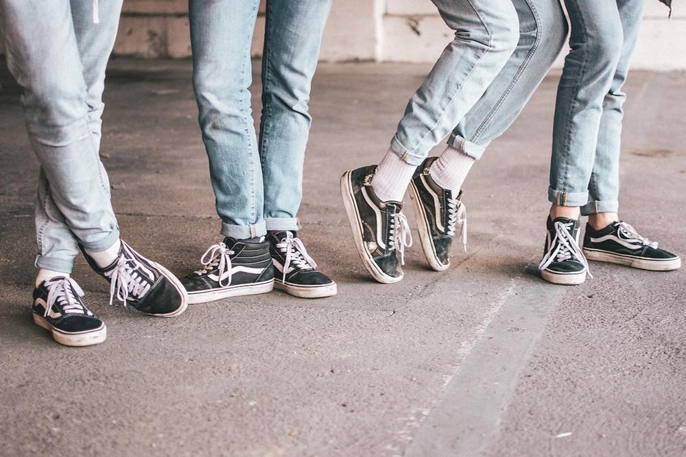 ผู้ชาย 4 คนใส่รองเท้า Van สีดำ แถบขาวเหมือนกัน