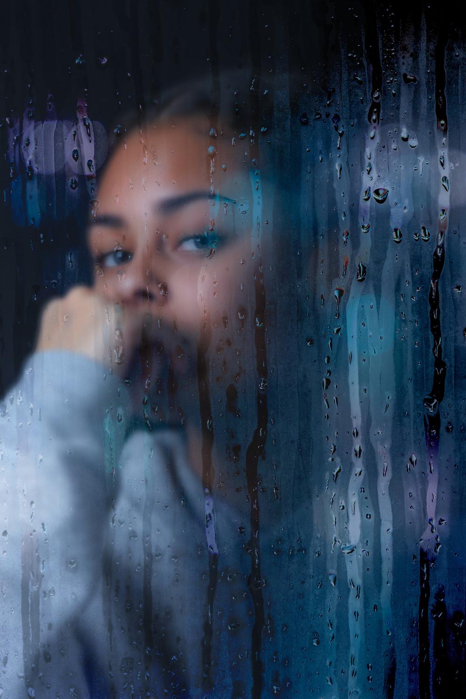 Rapariga triste junto janela com chuva