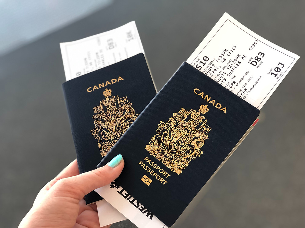 A hand holding two Canadian Passports. There are plane tickets sticking out the top of each passport.