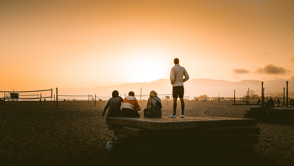 Four grieving teenagers stare at the skyline as the sun sets.