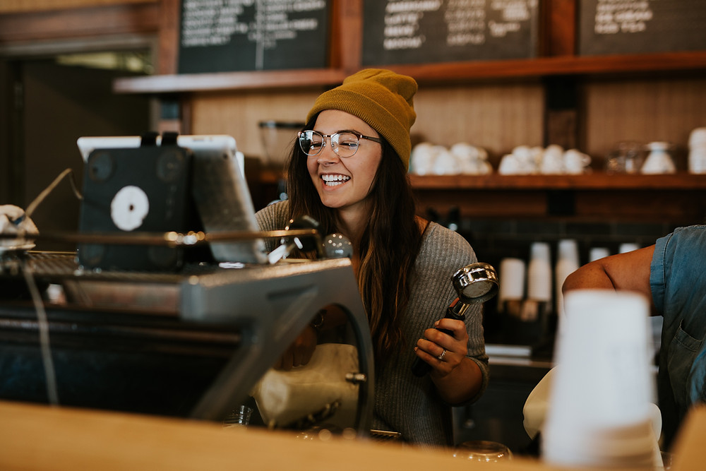 A friendly barista, who probably knows your name, manning the espresso machine.