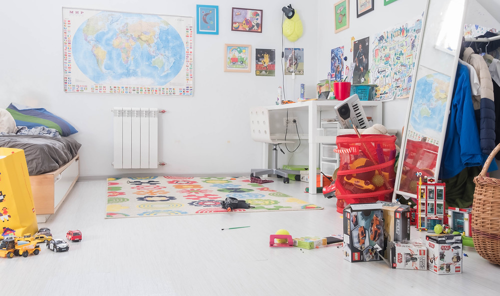 Messy kids room with toys on the ground and world map on wall.