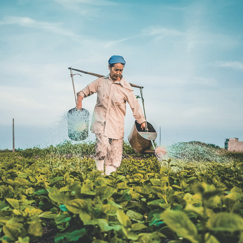 female farmer holding two watering cans over her shoulders