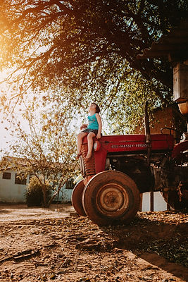 child sitting on red tractor