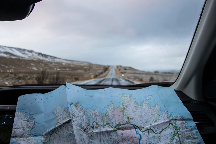 Person with a map spread out in a car driving the open road in the Great Plains