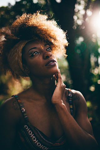 Women with hand on her face looking up | therapy for women | therapy for anxiety and perfectionism in Detroit, Mi 48075 | symptoms of anxiety | therapy for perfectionism | ptsd treatment and trauma therapy