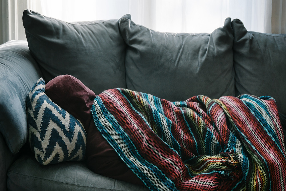 Person in a hoodie lying on a couch wrapped in a blanket feeling sick.