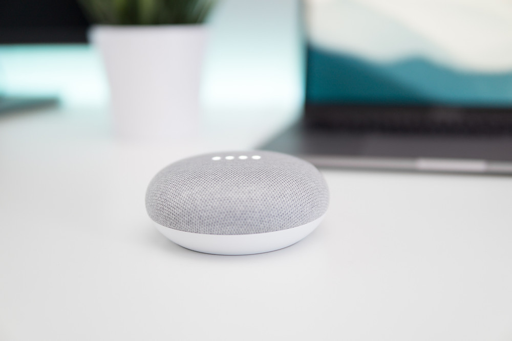 google small dot on a white desk. Blurred pc in the background