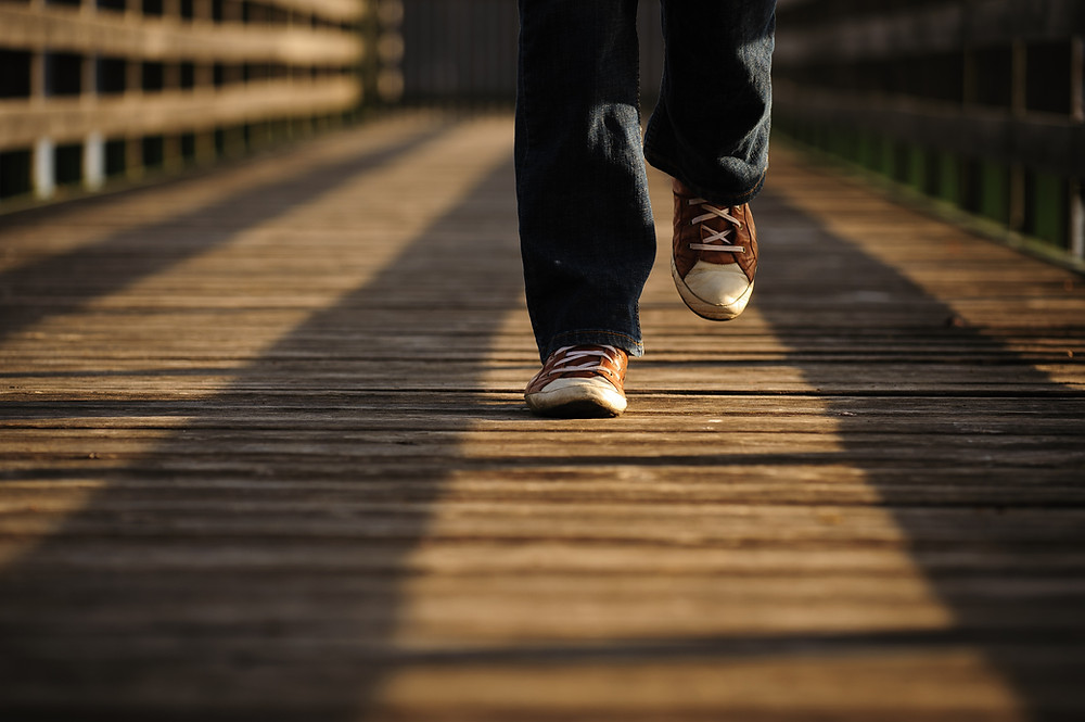 A person walks on a wooden pathway