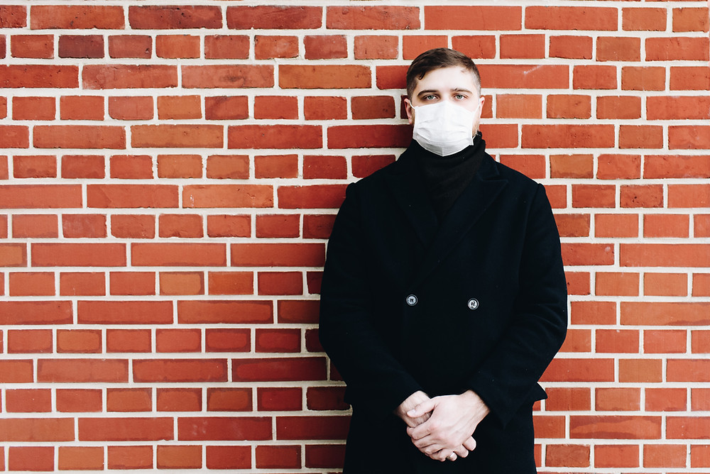 Man with mask in front of a red brick wall