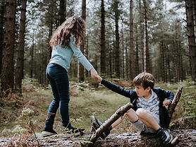 girl and boy in a forest. Boy is sitting on a fallen tree. Girl is helping the boy stand up.