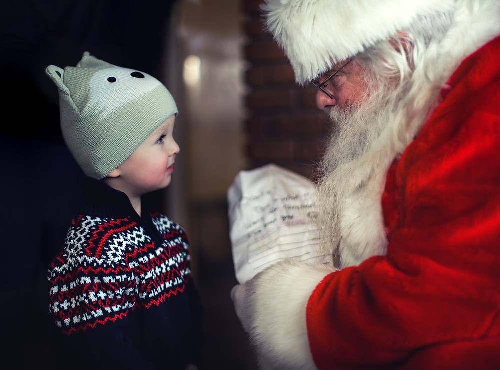 Little boy standing in front of Santa Claus, looking into each other's eyes. Little boy looks a little unsure