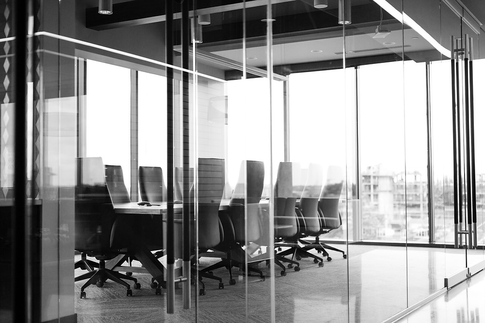black and white image of conference room table and chairs through a window
