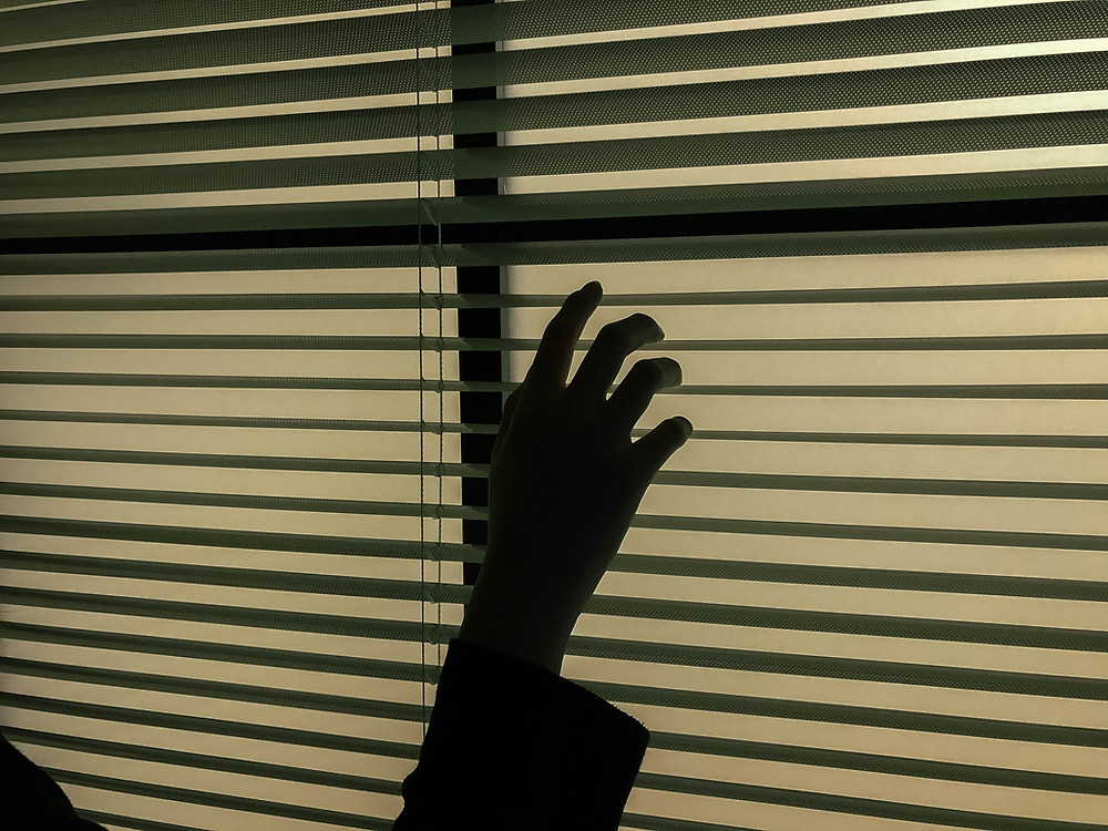 A hand holding blinds