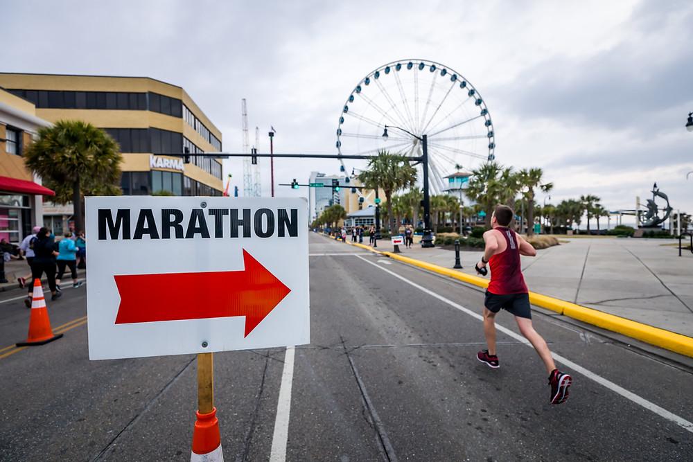 marathon runner going past a sign and toward a ferris wheel
