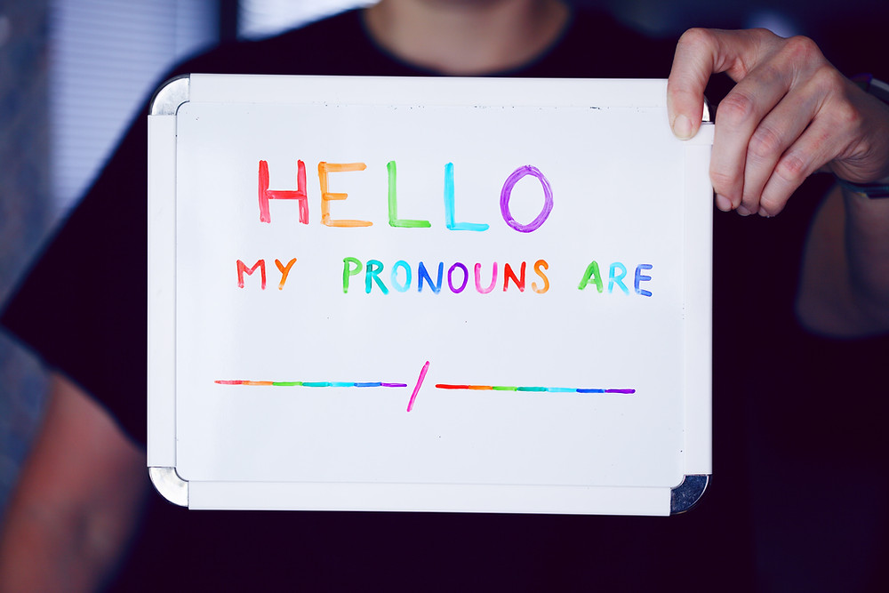 White board with colourful lettters on, which says 'Hello, my pronouns are .......""