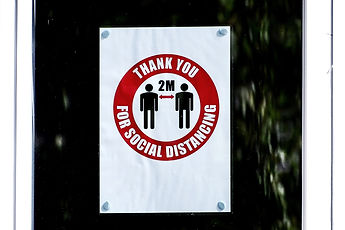 A Thank you for social distancing sign- that has two people standing in the middle of the sign with arrows indicating 2 Meters apart.