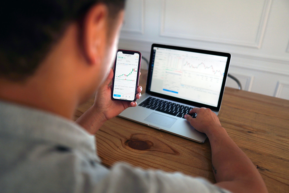 Day trader looking at his mobile charts and trading computer