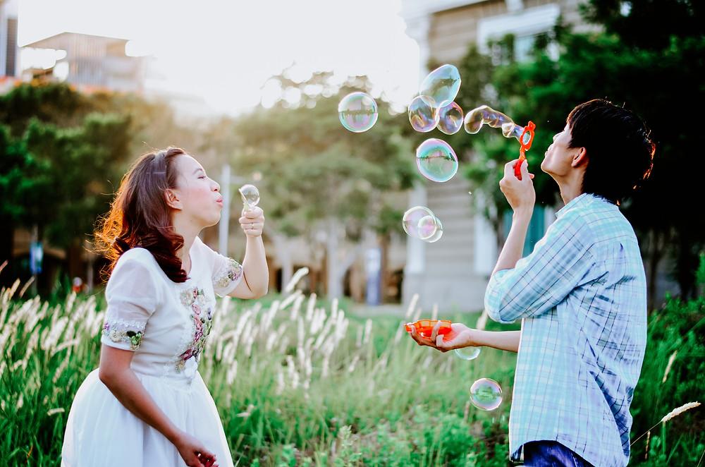 Bluetail_Travel_travel_agency_Arlington_VA_Couple blows bubbles in garden