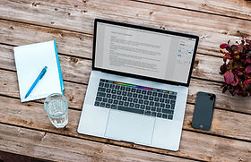 An open laptop on a wooden-slatted table, a glass of water, a notebook and pen, and a mobile phone.