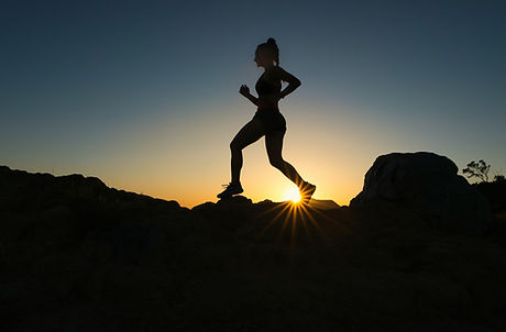 Woman in silhouette running on a mountain. Image by Cameron Venti
