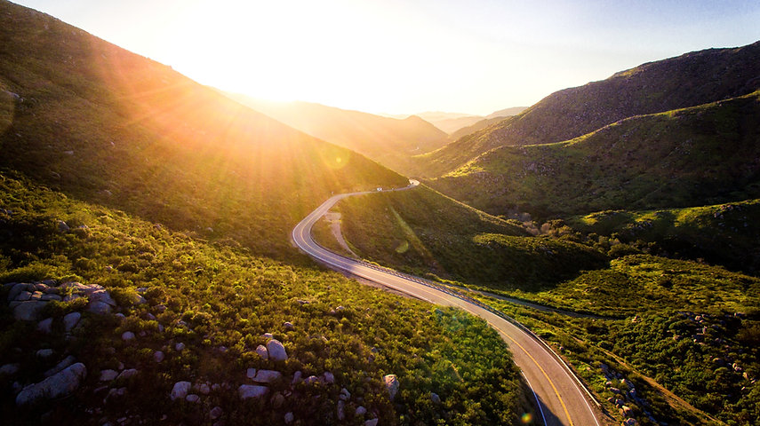 A sunny road between two mountains, symbolizing the journey individuals take in cousneling