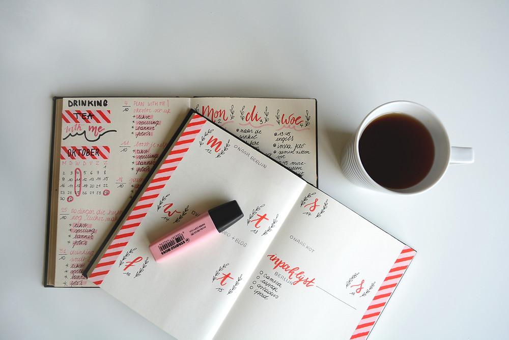 voller Terminkalender mit Kaffeetasse und Leuchtstift