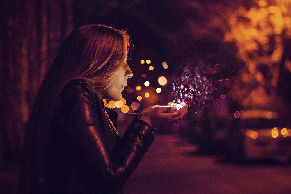 a woman blowing lit up sparkles into a dark background