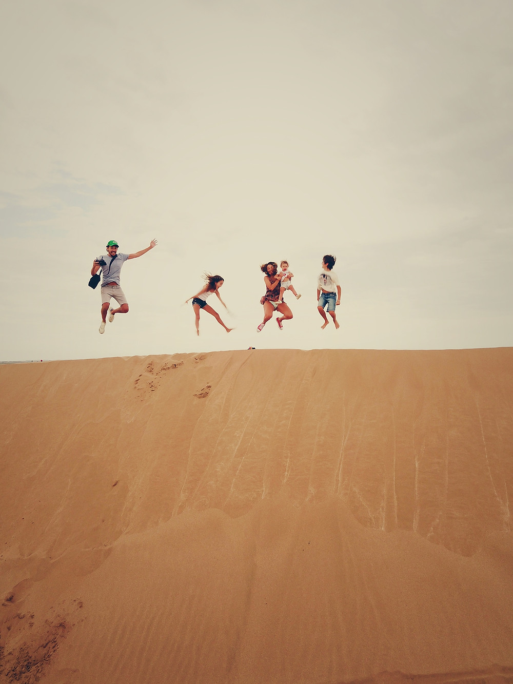 a family of 5 on holiday jumping in the air on top of a sand dune