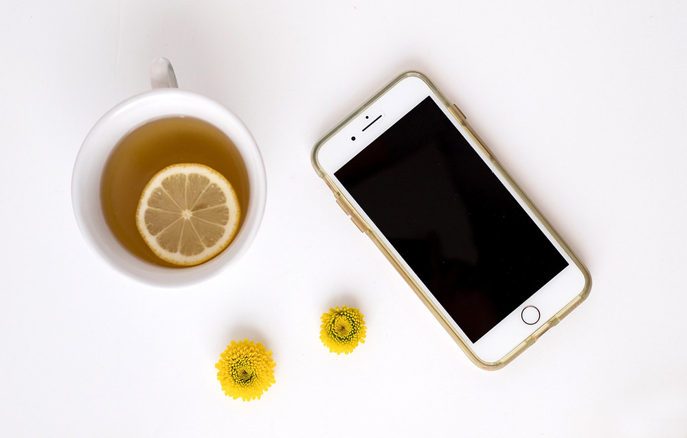 smartphone beside a lemon tea minimalist imagery