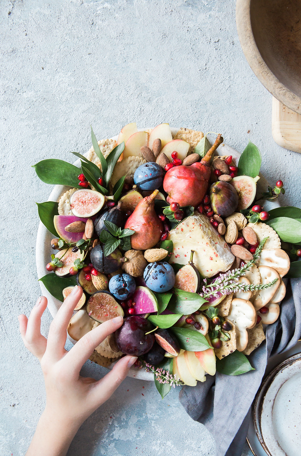 a bowl of food including figs, pears, plums, sliced apples, nuts and seeds, crackers and green leaves, a hand reaches in to pick up a purple plum