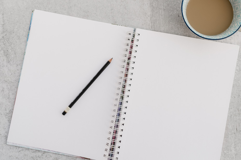 A white notebook with a pencil on top and a cup of coffee to the side.