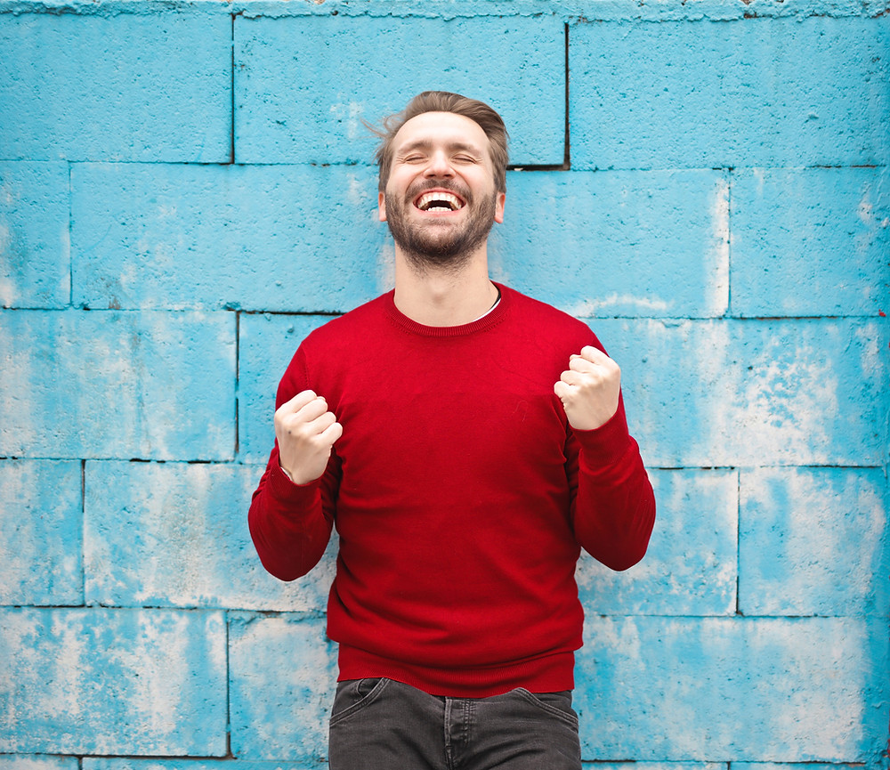 A Man in a Red Round Neck Sweater standing in front of a Pale Blue Block Wall.  He has his eyes closed and his head is tilted back with a large laugh on his face.  He has his arms up from the elbows with his fists clenched.  You could imagine he has just heard great news about a personal success.