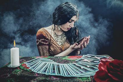 Tarot Card adn Oracle Reader Holding a Card