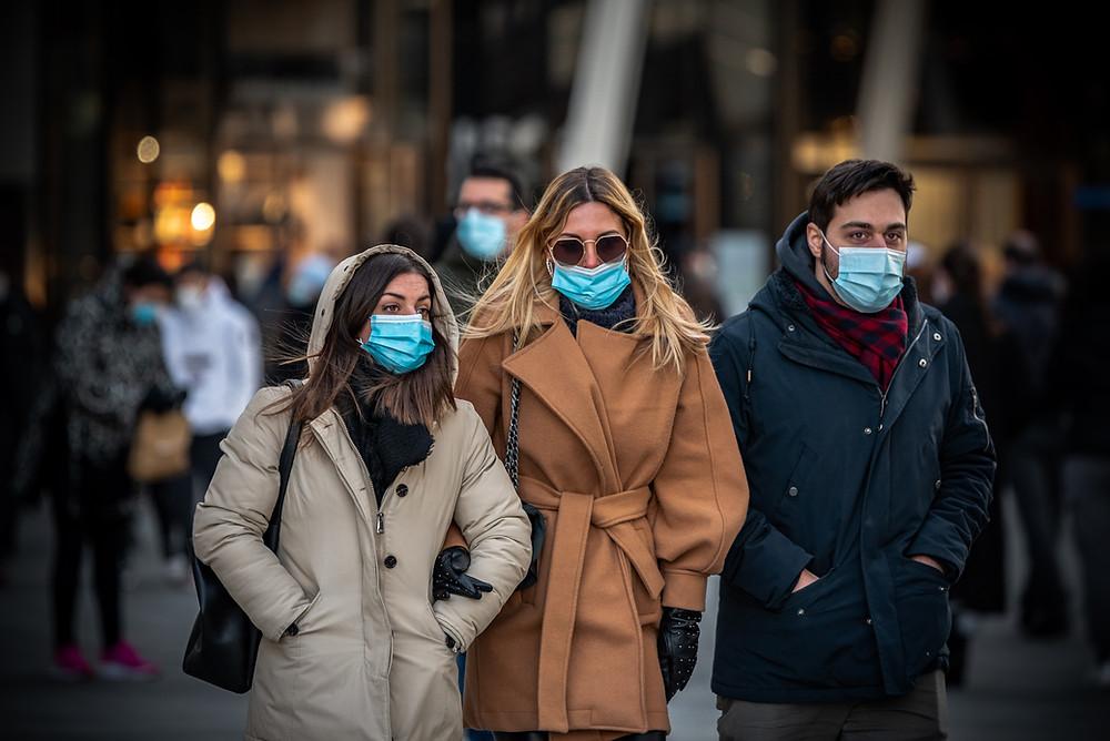 three early twenties walk with covid masks on