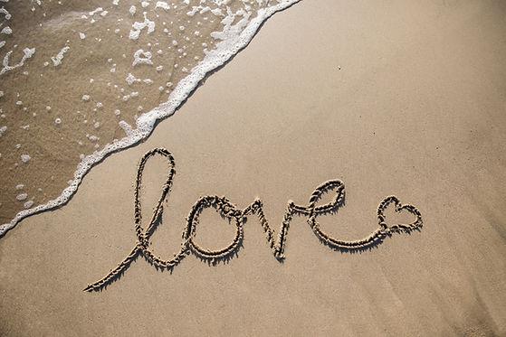 Love getekend in het zand met missie & visie van Hello Portugal Concepts